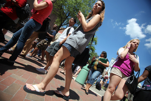 Norfolk students and Macarthur Mall patrons gather in the green space on Monticello Ave after being evacuated from buildings after an earthquake on Tuesday, Aug. 23, 2011, in Norfolk, Va. (AP Photo/The Virginian-Pilot, Steve Earley)