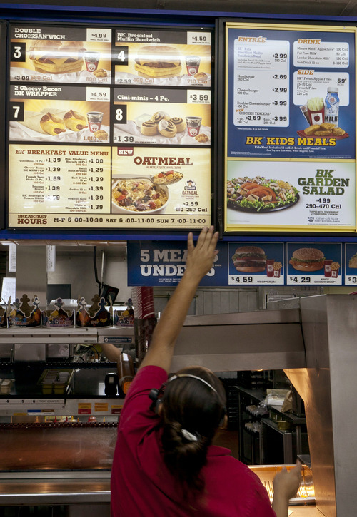 Damian Dovarganes  |  The Associated Press A Burger King employee adjusts the menu showing the new oatmeal item in Los Angeles on Wednesday. Burger King is adding oatmeal to its breakfast menu as the struggling fast-food chain tries to reinvent itself. The world's second-largest burger chain says the move balances out its menu to offer customers a healthier breakfast option.