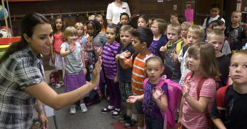 Al Hartmann  |  The Salt Lake Tribune First-graders at Horizon Elementary School in Murray sing their first song in Spanish with their Spanish speaking teacher Karina Guzman on the first day of school Monday August 22.  The class is dual immersion.     They spend the other half of their classroom experience with English speaking teacher Linda Curtis.