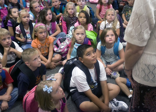 Al Hartmann  |  The Salt Lake Tribune First-graders at Horizon Elementary School in Murray listen intently to Linda Curtis, their English speaking teacher on the first day of school Monday August 22.  The class is dual immersion.     They spend the other half of their classroom experience with their Spanish speaking teacher Karina Guzman.