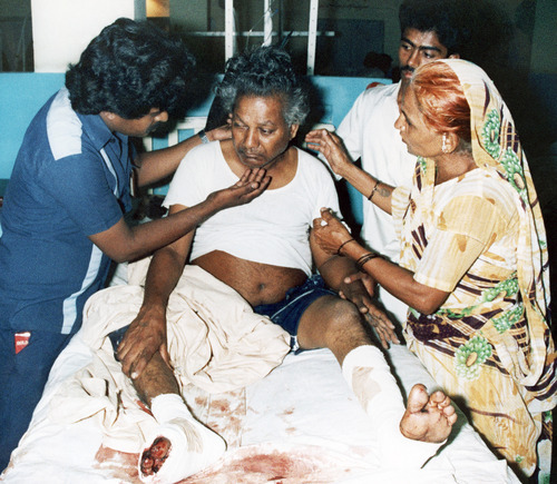 Mr. Jiwan Nagag from Karachi is comforted by a medical worker and by a relative in the Jinnah hospital in Karachi, Pakistan on Friday, Sept. 6, 1986. The Pakistani is among those wounded people, who were on the Pan Am flight that was hijacked and later was the scene of a shootout between the hijackers and army commandos. 14 people died in the shootout. (AP Photo/Michel Lipchitz)