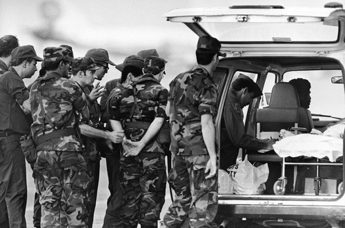 American soldiers stationed in West Germany line up behind an ambulance car on the tarmac of the Karachi airport in Pakistan on Saturday, Sept. 6, 1986. The soldiers arrived here to fly out the wounded people to Germany after they suffered injuries in the shootout on Friday in the hijacked Pan Am jetliner 073. (AP Photo/Liu Heung Shing) Eds. note: the shadow behind the soldiers is the Pan Am aircraft, that was hijacked.