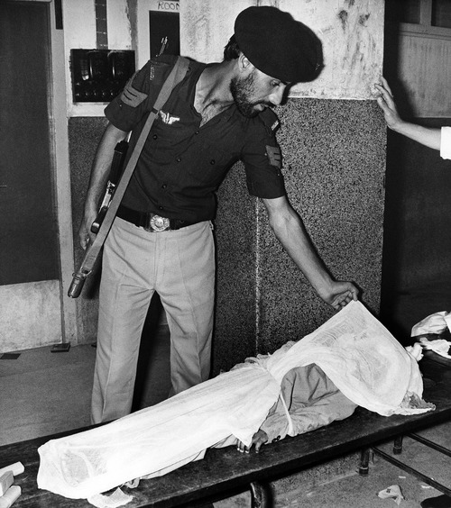 A Pakistani policeman corrects the cover of the dead body of a child in the Karachi , Pakistan, Jinnach Hospital on Friday, Sept. 6, 1986. This child is one of the 14 passengers of a Pan Am airliner that lost itís life during the shootout in the plane between hijackers and army commandos. More than 50 other people were injured and now under medical care in various hospital in Karachi. (AP Photo/Michel Lipchitz)