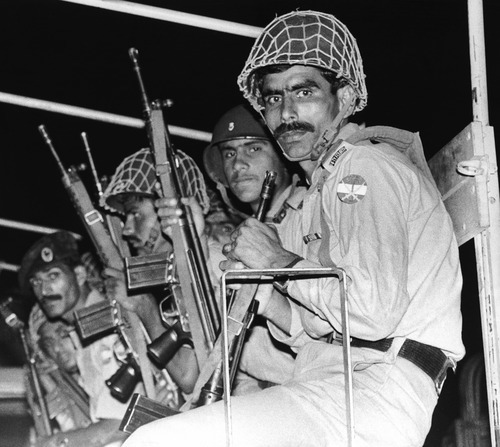 Pakistan army commandos with their automatic rifles ride the army truck as it entered the airport in Karachi, Pakistan on Friday, Sept. 6, 1986. After there was a power black out aboard the Pan Am plane, the hijackers began shooting the passengers and the army commandos stormed the plane and it resulted with 14 passengers killed and 2 hijackers dead. (AP Photo/Liu Heung Shing)