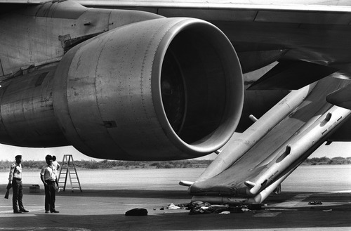 Pakistani policemen stand under the main engine and the emergency chute of the Pan Am jetliner 073 in Karachi on Saturday, Sept. 6, 1986, one day after it had been hijacked by a group of four. Some of the passengers and of the crew members escaped via the chute into freedom after a shootout broke out on the plane during a power blackout between the hijackers and an army commando. 14 people died, more than 100 were injured and hospitalized. (AP Photo/Michel Lipchitz)
