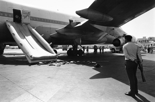 A Pakistan policeman stands with his rifle at the Pan Am jetliner under the emergency chute in Karachi, Pakistan on Saturday morning, Sept. 6, 1986. The American aircraft had been hijacked one day ago by a group of four and during a shootout on the plane 14 people died and more than other 100 passengers were injured. Underneath the chute, on which some passengers escaped, are some belongings of them still on the tarmac. (AP Photo/Michel Lipchitz)