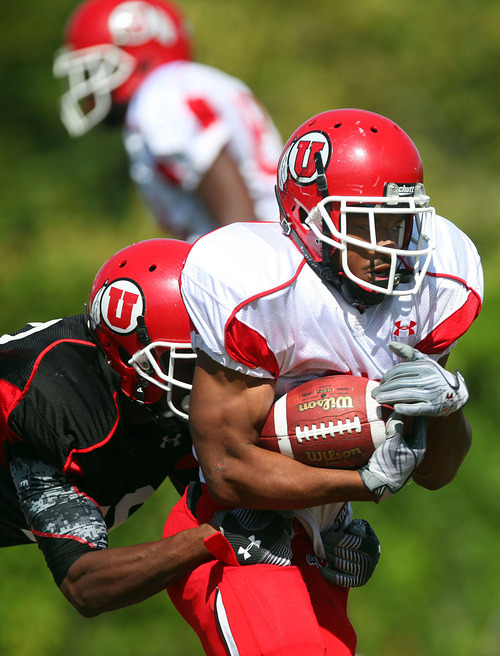 Lennie Mahler  |  The Salt Lake Tribune Utah's Eric Rowe holds on as John White IV rushes the ball during scrimmage Saturday, Aug. 13, 2011, at the Eccles practice field.