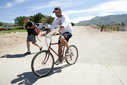 Chris Detrick  |  The Salt Lake Tribune Utah Ute coach Kyle Whittingham after rides his 1981 Diamond Back mountain bike after practice at the University of Utah on Thursday, Aug. 18, 2011.