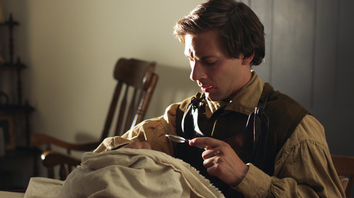 Joseph Smith (R. Dustin Harding)  translates the golden plates Tnto the Book of Mormon in a scene from