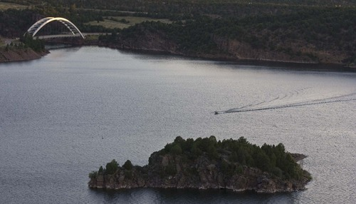 Paul Fraughton  |  The Salt Lake Tribune A boater cuts across Flaming Gorge Reservoir near the dam site on Wednesday,  Aug. 17, 2011.