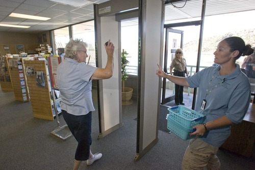 Paul Fraughton  |  The Salt Lake Tribune Shirley Card, a tour guide at Flaming Gorge Dam, gives instructions to a visitor going through a metal detector before going on a tour Thursday, Aug. 18, 2011.
