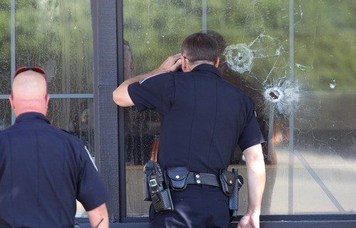 Officers look through a bullet-damaged window of an IHOP restaurant in Carson City, Nev., on Tuesday, Sept. 6, 2011. Three people were killed after a gunman opened fire at the restaurant, authorities said. (AP Photo/Cathleen Allison)