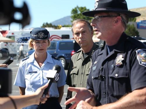 Nevada National Guard Press Information Officer April Conway, left, and Carson City Sheriff Ken Furlon, center, listen to Trooper Chuck Allen at a news conference following a shooting in an IHOP restaurant in Carson City, Nev., on Tuesday, Sept. 6, 2011.  A gunman with a rifle opened fire at a International House of Pancakes restaurantkilling three people including two uniformed National Guard members and himself, and wounding six others in a hail of gunfire during the morning breakfast hour, authorities and witnesses said.  (AP Photo/Cathleen Allison)