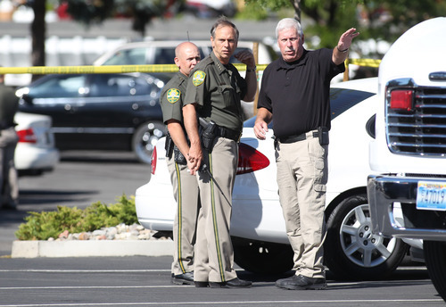 Carson City Sheriff Ken Furlong, center, and Undersheriff Steve Albertson, right, confer at the scene of a shooting at an IHOP restaurant in Carson City, Nev., on Tuesday, Sept. 6, 2011. Three people were killed after a gunman opened fire at the restaurant, authorities said. (AP Photo/Cathleen Allison)