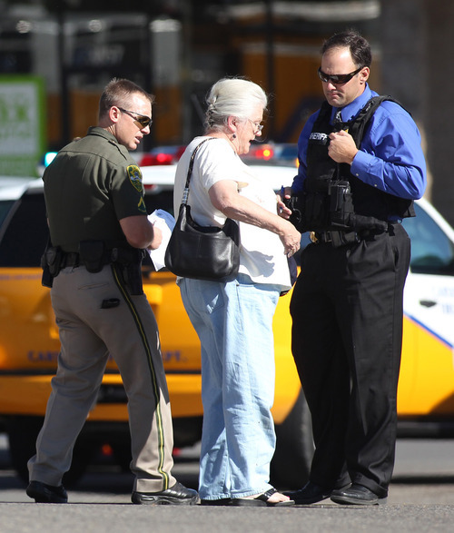 Emergency personnel talk to an unidentified woman as they respond to a shooting at an IHOP restaurant in Carson City, Nev., on Tuesday, Sept. 6, 2011. Three people were killed after a gunman opened fire at the restaurant, authorities said. (AP Photo/Cathleen Allison)