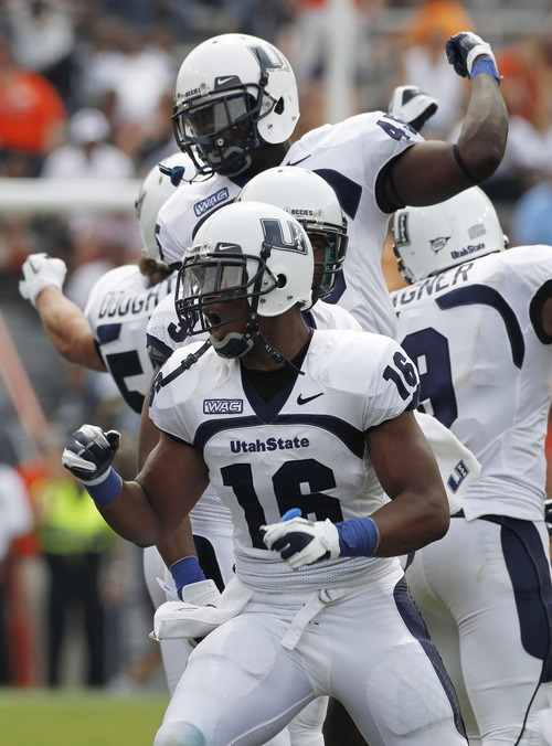 Utah State quarterback Chuckie Keeton (16) reacts with teammates after scoring during a 42-38 loss to Auburn in an NCAA college football game in Auburn, Saturday, Sept. 3, 2011.  (AP Photo/Dave Martin)