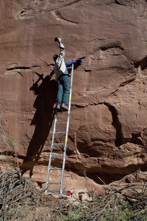 Archeologist Henry Wallace photographs a rock art panel believed to contain petroglyphs of mammoths.  Courtesy Ekkehart Malotki