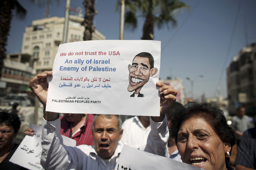 A Palestinian man holds a sign protesting US involvement in the Middle East, in the West Bank city of Ramallah, Wednesday, Sept. 7, 2011. Two senior White House envoys, David Hale and Dennis Ross, arrived in the region on Tuesday for talks with Israel and Palestinian officials. The U.S. has been trying to persuade the Palestinians to drop their plan to ask the U.N. this month to approve their independence and instead resume peace talks with Israel.(AP Photo/Tara Todras-Whitehill)