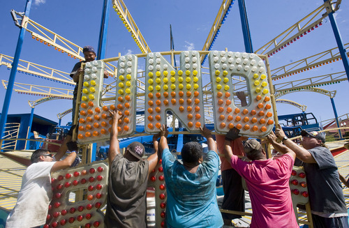 Al Hartmann | The Salt Lake Tribune Carnival workers set up the electric sign for the Thunderbolt ride at the Utah State Fairpark last week. The Utah State Fair opens Sept. 8.
