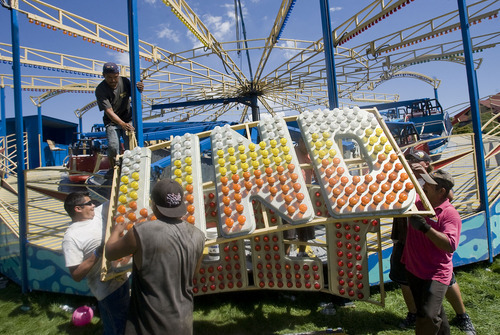 Al Hartmann  |  The Salt Lake Tribune Carnival workers set up the electric sign for the Thunderbolt ride at the Utah State Fairpark on Aug. 30.  Carnival rides are being set up, tents raised, and vendor booths are getting prepared for the opening of the Utah State Fair on Sept. 8.