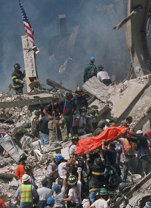Emergency personnel carry an orange body bag with the remains of a victim of the World Trade Center crash from the rubble, Thursday, September 13, 2001. Two hijacked airliners were crashed into the towers of the World Trade Center on Tuesday, Sept. 11, destroying both buildings. (Bill Farrington/The Associated Press)