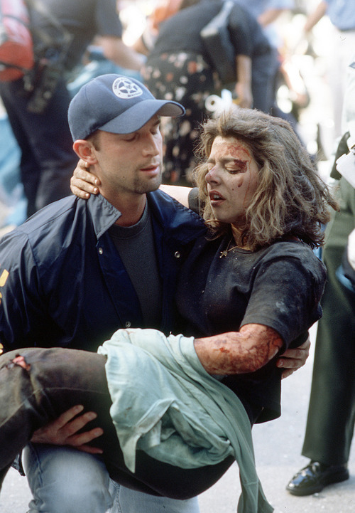 Deputy U.S. marshal Dominic Guadagnoli helps a women after she was injured in the terrorist attack on the World Trade Center in New York, Tuesday, Sept. 11, 2001. (Gulnara Samoilova/The Associated Press)