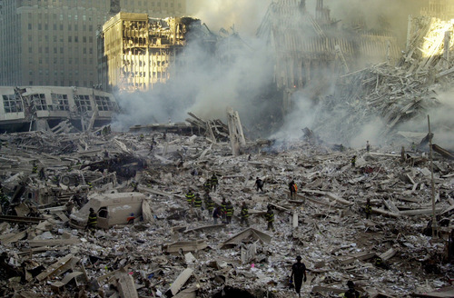 Firefighters walk through smoldering debris at the site of the World Trade Center in New York Tuesday, Sept. 11, 2001. Two planes crashed into the upper floors of both World Trade Center towers minutes apart Tuesday morning, collapsing the 110-story buildings. (Graham Morrison/The Associated Press)