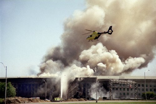 A helicopter flies over the Pentagon in Washington, Tuesday, Sept. 11, 2001 as smoke billows over the building. The Pentagon took a direct, devastating hit from an aircraft and the enduring symbols of American power were evacuated as an apparent terrorist attack quickly spread fear and chaos in the nation's capital. (Heesoon Yim/The Associated Press)