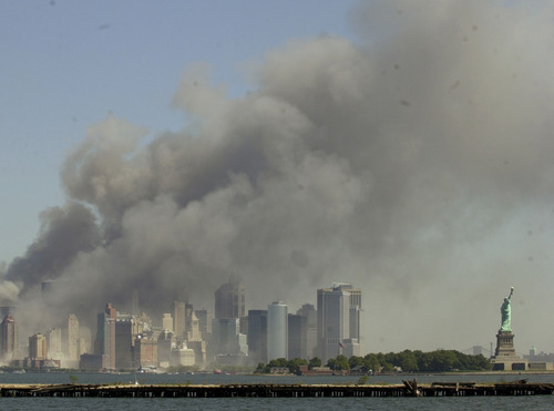 The Statue of Liberty, right, stands at the entrance to New York Harbor as the twin towers of the World Trade Center burn in this view from Jersey City, N.J., Sept. 11, 2001. (Mike Derer/The Associated Press)