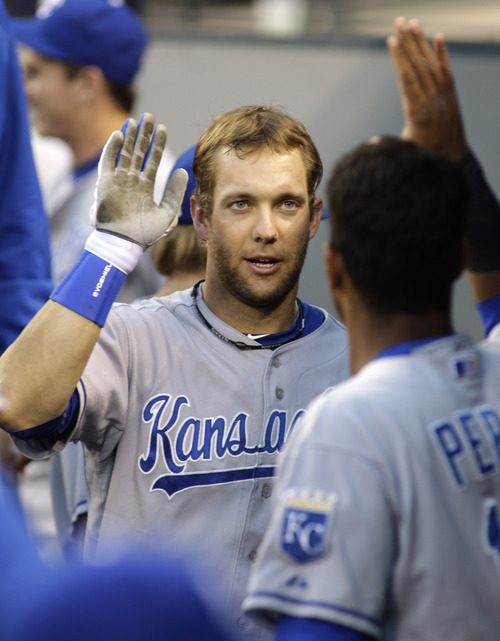 Kansas City Royals' Alex Gordon is greeted in the dugout after he hit a solo home run against the Seattle Mariners in the first inning of a baseball game, Friday, Sept. 9, 2011, in Seattle. (AP Photo/Ted S. Warren)