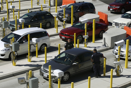 U.S. Customs and Border Protection officers walk through cars waiting to enter the United States from Canada, Wednesday, Sept. 7, 2011, near Blaine, Wash. The increased focus on border security since the Sept. 11, 2001 terrorist attacks has led to tensions between the government and local residents in the area. (AP Photo/Ted S. Warren)