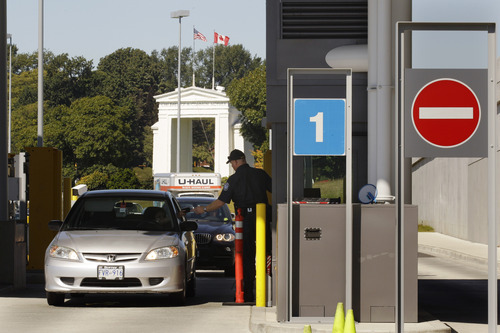 With the Peace Arch in the background, a U.S. Customs and Border Protection officer checks cars and people entering the United States from Canada, Wednesday, Sept. 7, 2011, near Blaine, Wash. The increased focus on border security since the Sept. 11, 2001 terrorist attacks has led to tensions between the government and local residents in the area. (AP Photo/Ted S. Warren)
