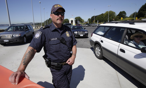 U.S. Customs and Border Protection supervisor Scott Lazalde watches cars waiting to enter the United States from Canada, Wednesday, Sept. 7, 2011, near Blaine, Wash. The increased focus on border security since the Sept. 11, 2001 terrorist attacks has led to tensions between the government and local residents in the area. (AP Photo/Ted S. Warren)