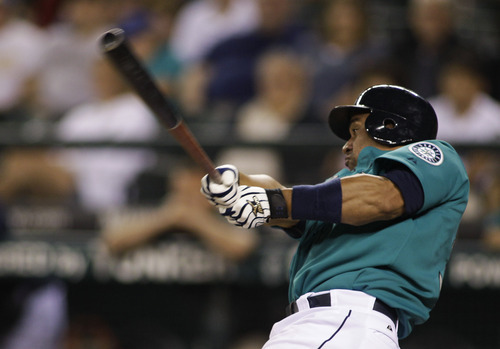 Seattle Mariners' Miguel Olivo hits a triple during the fifth inning of a baseball game against the Kansas City Royals, Friday, Sept. 9, 2011, in Seattle. (AP Photo/Ted S. Warren)