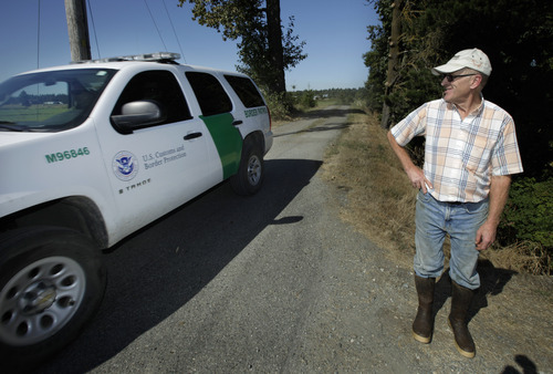 Dairy farmer Larry DeHaan, right, looks on as a Border Patrol vehicle passes his farm, Wednesday, Sept. 7, 2011, near Lynden, Wash. Further up the road, DeHaan has put up a sign asking government vehicles, to stay off of the portion of the road that is on his private property. The increased focus on border security since the Sept. 11, 2001 terrorist attacks has led to tensions between the government and local residents in the area. (AP Photo/Ted S. Warren)