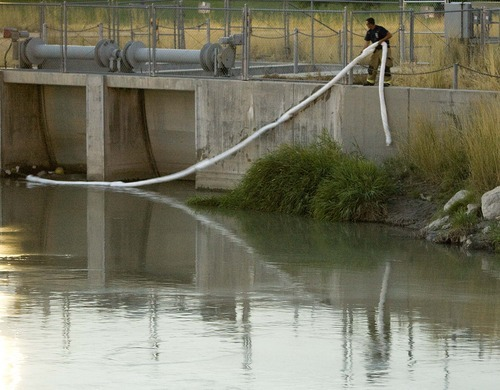 Trent Nelson  |  The Salt Lake Tribune A firefighter drops a boom into place in the Jordan River near 2100 South to stem a spill in Salt Lake City on Saturday.