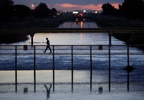 Trent Nelson  |  The Salt Lake Tribune With the lights of rescue crews in the background, a firefighter crosses a bridge on the Jordan River near 2100 South while working to stem a spill in Salt Lake City on Saturday.