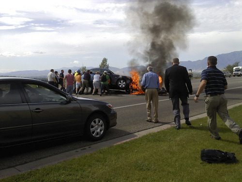 Witnesses help lift a burning car off an injured motorcyclist Monday morning in Logan.  Credit: Kelley Sandall