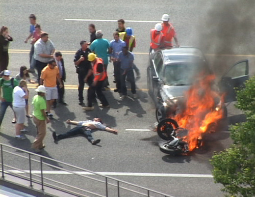 In this Monday, Sept. 12, 2011 image taken from video, a group of people are directed away from the scene by police after tilting a burning BMW up to free Brandon Wright, on his back on the ground, who was pinned underneath after he collided with the car while riding his motorcycle on U.S. 89 in Logan, Utah. Authorities said Wright was riding his motorcycle near the Utah State University campus in Logan when the 21-year-old collided with the BMW that was pulling out of a parking lot. Tire and skid marks on the highway indicate that Wright laid the bike down and slid along the road before colliding with the car, Assistant Police Chief Jeff Curtis said. (AP Photo/Chris Garff)