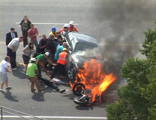 In this Monday, Sept. 12, 2011 image taken from video, a group of people tilt a burning BMW up to free Brandon Wright, on his back on the ground, who was pinned underneath after he collided with the car while riding his motorcycle on U.S. 89 in Logan, Utah.  Authorities said Wright was riding his motorcycle near the Utah State University campus in Logan when the 21-year-old collided with the BMW that was pulling out of a parking lot. Tire and skid marks on the highway indicate that Wright laid the bike down and slid along the road before colliding with the car, Assistant Police Chief Jeff Curtis said. (AP Photo/Chris Garff)