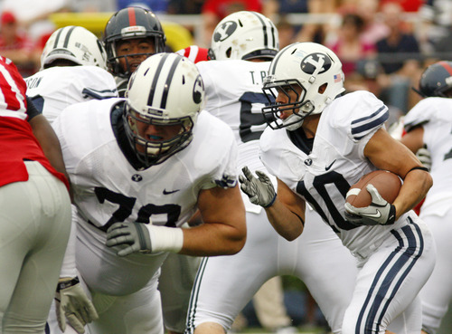 BYU running back JJ Di Luigi (10) follows teammate Houston Reynolds (78) in the match against Mississippi last week in Oxford, Miss. The Cougars are facing warm and dry conditions in the game against the Texas Longhorns Saturday.  (AP Photo/Rogelio V. Solis)