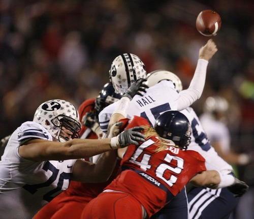 Tribune file photo BYU OL Matt Reynolds (70) blocks Arizona's Brooks Reed while BYU QB Max Hall (15) launches a pass at the Las Vegas Bowl, BYU vs. Arizona in 2008.