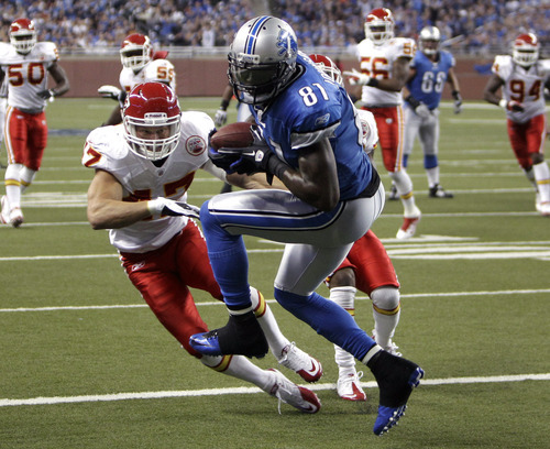 Detroit Lions wide receiver Calvin Johnson (81) catches a 15-yard touchdown reception as Kansas City Chiefs defensive back Jon McGraw (47) defends in the first quarter of an NFL football game in Detroit, Sunday, Sept. 18, 2011. (AP Photo/Paul Sancya)