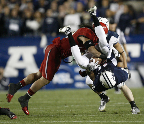 Trent Nelson   The Salt Lake Tribune  BYU wide receiver Ross Apo (11) is tackled by Utes linebacker Chaz Walker (32) during BYU's game against Utah at Lavell Edwards Stadium in Provo, Utah September 17, 2011.