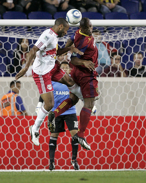Rich Schultz  |  The Associated Press New York Red Bulls' Thierry Henry, left, fights Real Salt Lake's Jamison Olave, right, for the ball in front of Real Salt Lake's goalkeeper Nick Rimando (18) during the first half of a soccer game at Red Bull Arena in Harrison, N.J., Wednesday.