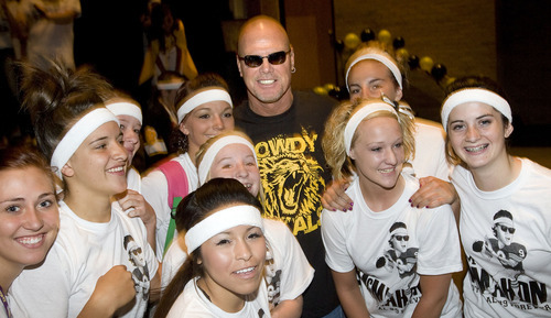Al Hartmann  |  The Salt Lake Tribune Roy High School students gather Friday morning for a pep rally September 16 to honor former alumni Jim McMahon who went on to quarterback for BYU and the Chicago Bears in the NFL.  He poses for a picture with some members of the school dance group.   His jersey will be retired Friday night during a game with Box Elder High School.