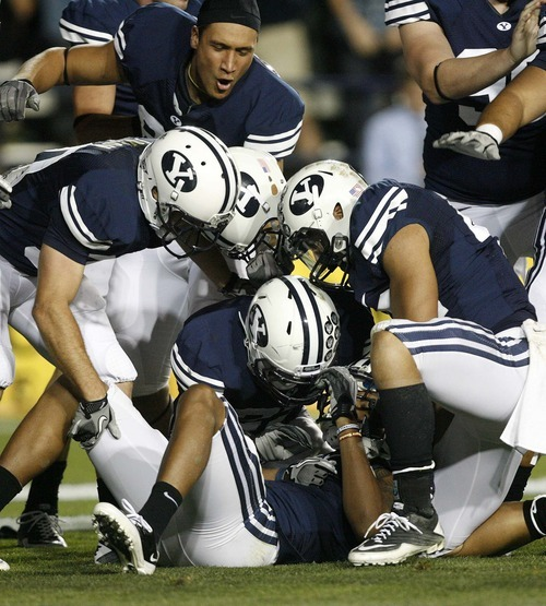 Trent Nelson  |  The Salt Lake Tribune BYU players dogpile on Cody Hoffman (2) after his kick return touchdown. BYU vs. Central Florida, college football at LaVell Edwards Stadium in Provo, Utah, Friday, September 23, 2011.