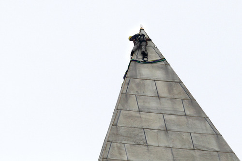A man attaches rigging to the top of the Washington Monument on the National Mall, in Washington, Tuesday, Sept. 27, 2011, before engineers rappeled down the sides of the monument to survey the extent of damage sustained to the monument from the Aug. 23 earthquake.  (AP Photo/Jacquelyn Martin)