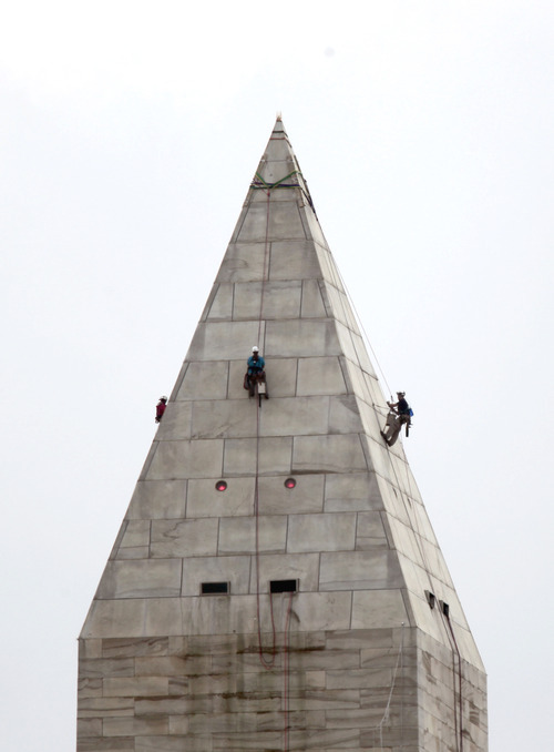 A team of engineers, from left, Emma Cardini, Katie Francis and Erik Sohn, harnessed to ropes , inspect the exterior of the Washington Monument for damage caused by last months earthquake, Wednesday, Sept. 28, 2011, in Washington.  (AP Photo/Pablo Martinez Monsvais)