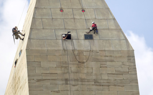 Evan Vucci  |  The Associated Press A team of engineers, from left, Dan Gach, Emma Cardini, center, and Katie Francis, harnessed to ropes, inspect the exterior of the Washington Monument in Washington, D.C., on Wednesday for damage caused by last month's earthquake.